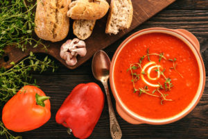 bread, paprika, tomato soup neatly arranged on a table